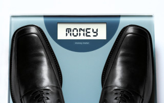 "Business value and money concept conveyed via businessman stepping on a ""money weighing machine"""