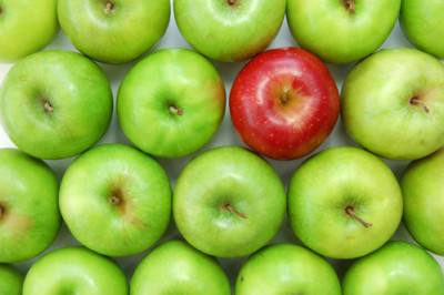 Red apple amongst many green ones